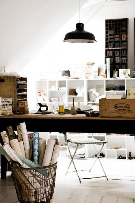 Studio space for artist or writer. Large paper rolls in bin. Wood floors and tables. Industrial lamp. Letterpress letters on wall. Organized shelves.