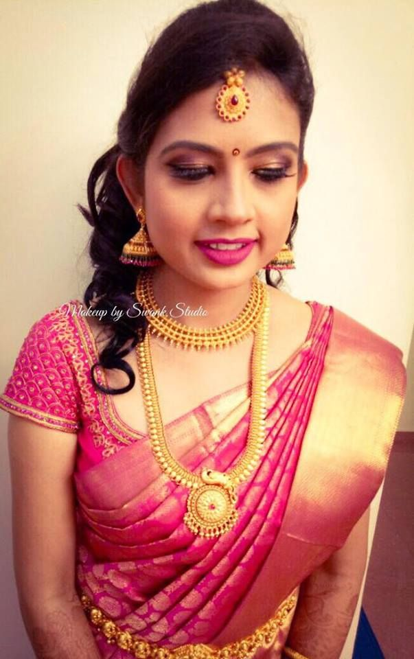 Traditional Southern Indian bride, Sahana wears bridal silk saree and jewellery for her reception. Makeup and hairstyle by Swank Studio. Pink lips. Jhumkis. South Indian bride. Eye makeup. Bridal jewelry. Bridal hair. Silk sari. Bridal Saree Blouse Design. Indian Bridal Makeup. Indian Bride. Gold Jewellery. Statement Blouse. Tamil bride. Telugu bride. Kannada bride. Hindu bride. Malayalee bride. Find us at https://www.facebook.com/SwankStudioBangalore