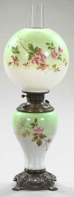 lighting, America, An American polychromed white opal glass kerosene parlor lamp,  in the rococo taste, with broonze-patinated brass mounts, the vasiform glass body and spherical glass shade polychrome with wild rose spras on a pale-green-to-white background, the blown glass chimney retained in the conversion to electric. Circa 1875-1900