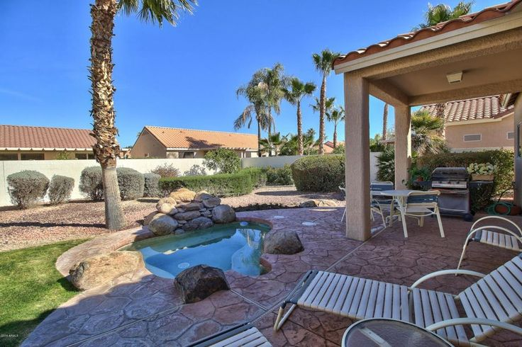 Southwestern Hot Tub with exterior stone floors, Fence, Outdoor kitchen
