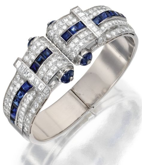 An Art Deco Platinum, Diamond, Sapphire and Synthetic Sapphire Bangle-Bracelet, Circa 1925. The hinged bangle set at the front with old European-cut, single-cut and baguette diamonds weighing approximately 8.00 carats, accented by cabochon and calibré-cut sapphires and synthetic sapphires. #ArtDeco #bracelet