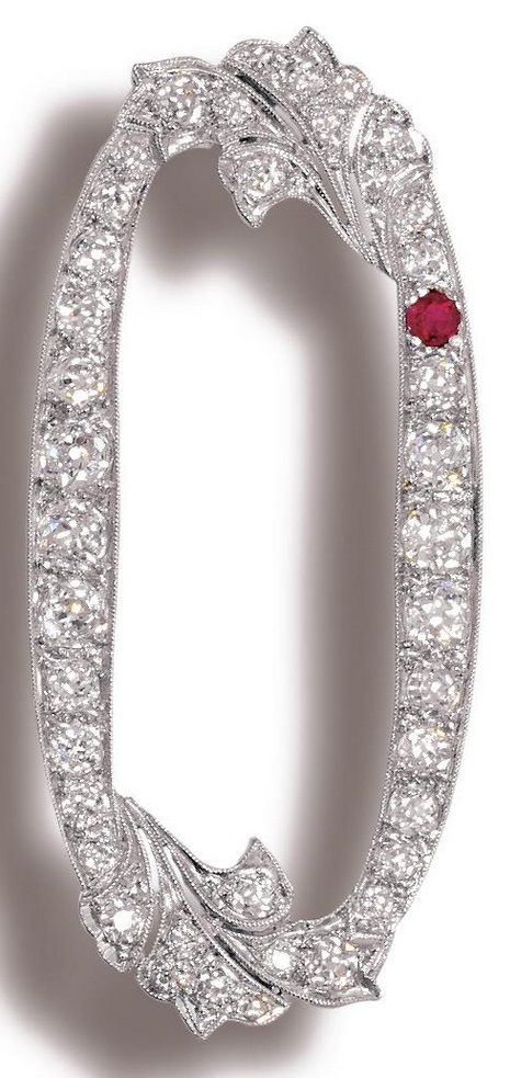 An Art Deco ruby and diamond brooch, circa 1920. The openwork oval brooch decorated with foliate motifs, set throughout with circular-cut diamonds and one ruby. #ArtDeco #brooch