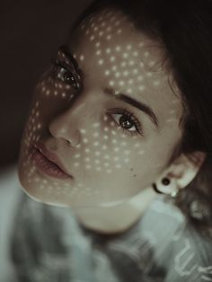 What caught my attention to this photo is the way the light hits her face, its very different. Also her eyes are beautiful and it gives the picture a calm look.