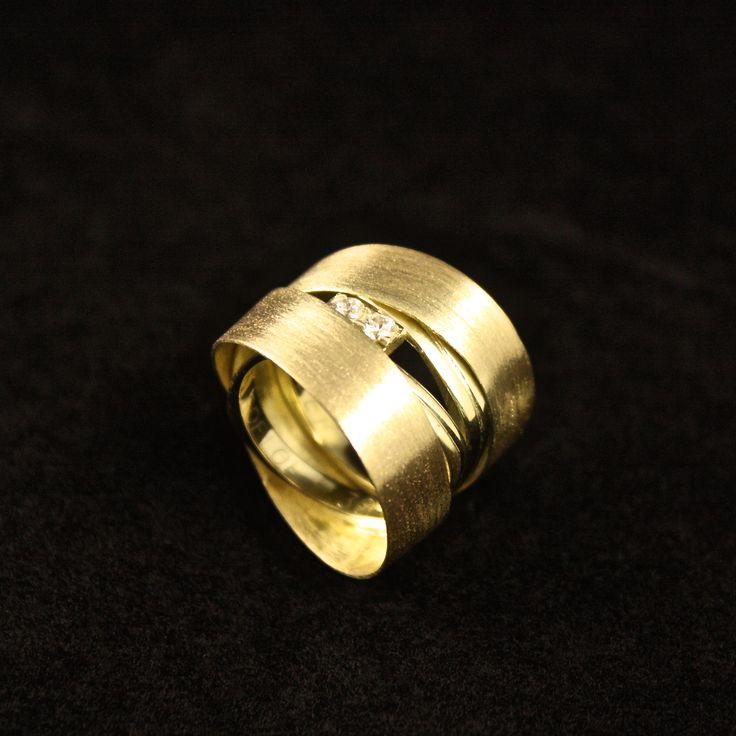 Gouden damesring met 2x Cubic Zirkonia's. Deze bijzonder mooie damesring is vervaardigd van 2x Trouwringen en een oud armbandje, wat is omgesmolten en gesmeed is tot de band die om de Trouwringen zit. De Cubic Zirkonia's zijn ook weer gebruikt in de ring.