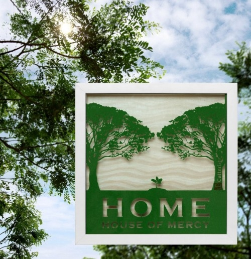 Paper Cutting: Logo HOME (House of Mercy)  Dua pohon dengan ranting-ranting dahannya membentuk atap rumah. Lalu di bawah dua pohon itu terdapat pohon kecil berwarna hijau lebih muda yang baru tumbuh (tunas baru). Di bawah naungan pohon-pohon pembentuk atap, kelak tunas itu akan menjadi pohon dengan ranting-ranting besar.