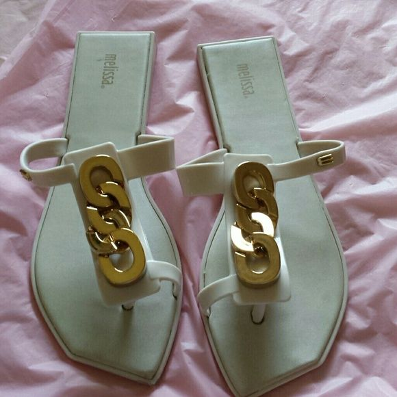 Melissa  Flip Flop Sandals With Toe Glove White jelly flip flop sandals with gold tone chain accents. Small wear spot front tip right sandal. Melissa  Shoes Sandals