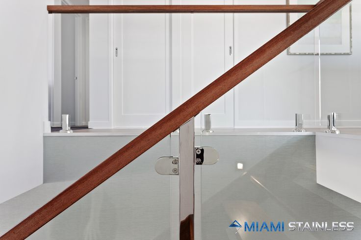 Glass balustrade with timber handrail and rectangle hollow posts with glass clamps