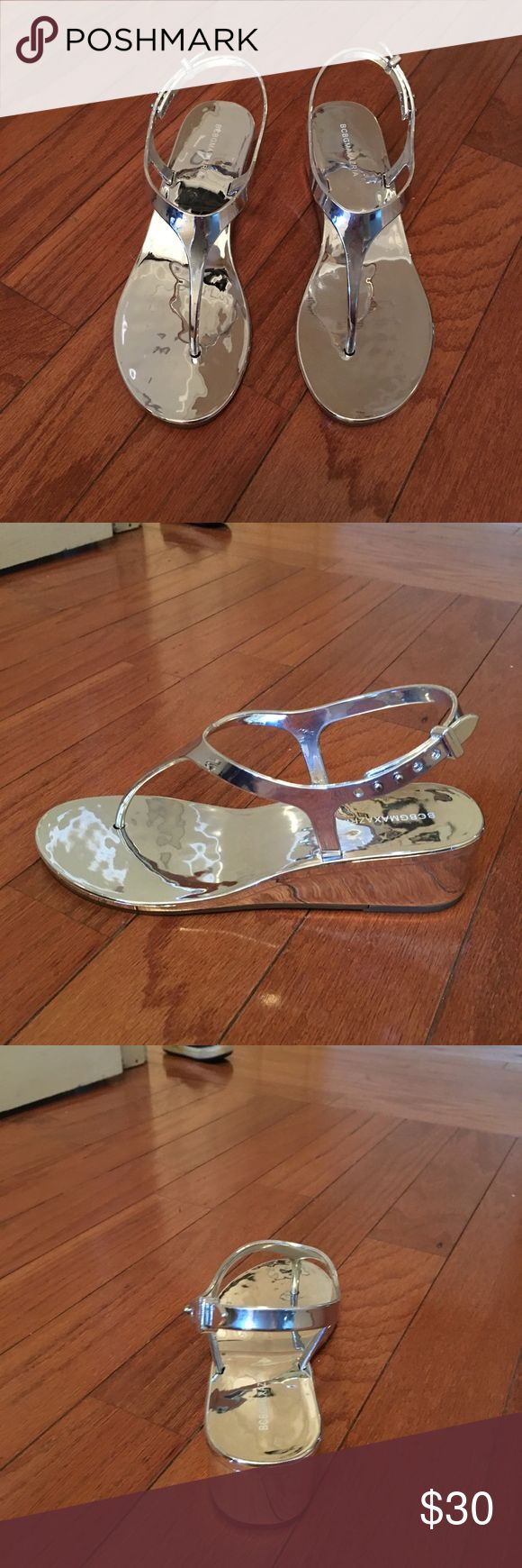 Silver wedge sandals BCBGMAXAZRIA Step into a stylish new season with these elegant, metallic-finished sandals rounding off your looks.  Thong toe. Mid heel. Mirrored metallic finish throughout. Ankle strap with adjustable side-buckle closure. BCBGMaxAzria Shoes Sandals