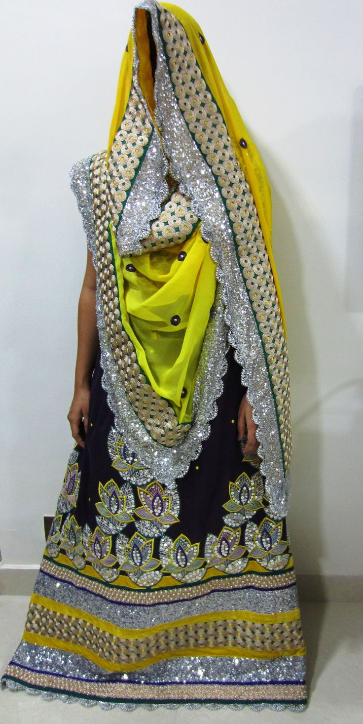 Description - Dazzling royal purple rida cum jodi designed using sequined, pearl, dori and crochet laces along with silver sequined flower appliques and velvet trims, teamed up with a contrast, shaded sunshine yellow dupatta with all over motifs. A stylized, glittery designer wear perfect for weddings / occasions  !