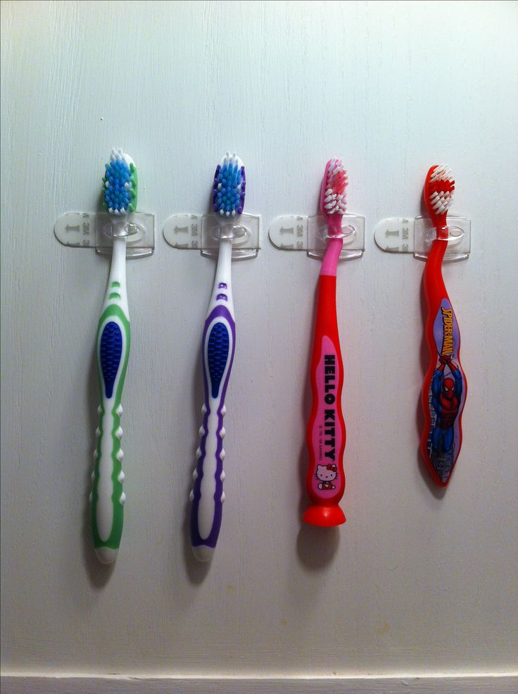 """Small bathroom counter? Use Command™ Mini Clear Hooks to hang toothbrushes on the inside of the medicine cabinet and """"clear"""" up counter space! *Remember- hang the hooks sideways."""