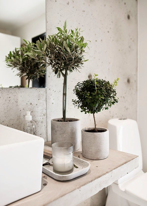 If you're not quite ready to go all-in on a concrete floor, consider picking up a few small pieces of decor to play with the trend without making a big commitment. The concrete planters and catchall tray in this pared-back bathroom are just a few examples of the endless concrete decor items available to take your style to the next level. Read more at: https://nyde.co.uk/blog/springs-concrete-trend/