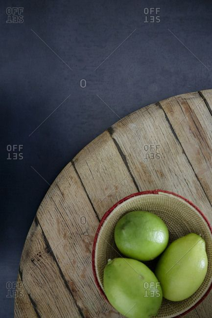Limes in a bowl on a wooden table