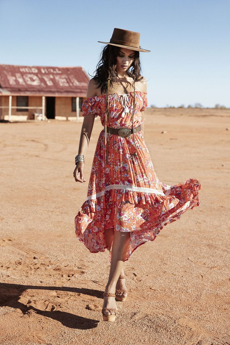 Off shoulder floaty floral bohemian midi length dress with brown leather western style belt and hat.