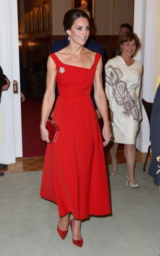 In Victoria, The Duchess wears a stunning scarlet, asymmetrical Preen midi-gown, accented by the Queen's sparkling Maple Leaf Diamond Brooch. Behind her is Premier Christy Clark. Photo: Canadian Heritage.