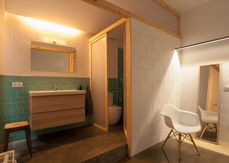 The bathrooms are open to the rest of the space, with the showers and toilets separated by a translucent screen.  Twin House by Nook Architects,