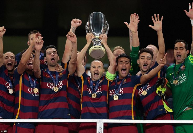 Barcelona captain Andres Iniesta lifts the UEFA European Super Cup up above his head as his delighted team-mates celebrate