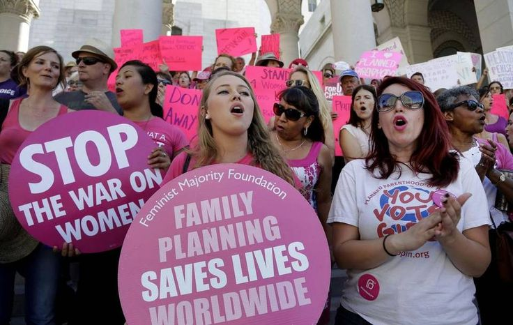 "Planned Parenthood supporters rally for women's access to reproductive health care on ""National Pink Out Day'' at Los Angeles City Hall. One of President-elect Donald Trump's first, and defining, acts next year could come on Republican legislation to cut off taxpayer money from Planned Parenthood."