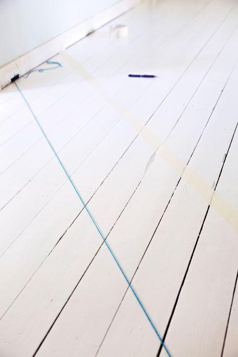 """[Del 1.] """"Börja med att tejpa listerna om du inte ska måla om dem efteråt. Slipa och tvätta golvet med målartvätt om det behövs. Måla därefter hela golvet med vit linoljefärg som grundfärg. När färgen har torkat är det dags att börja mäta upp rutorna. Fäst ett snöre i 45 graders vinkel från ett hörn och tvärs över golvet. Måla små blyertsstreck längs med snöret. Plocka bort snöret och tejpa längs markeringarna""""   Emmy Lundström, Gård & Torp"""