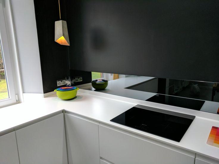 Kitchen, grey mirror splashback, concrete lamp, black walls, matte white units