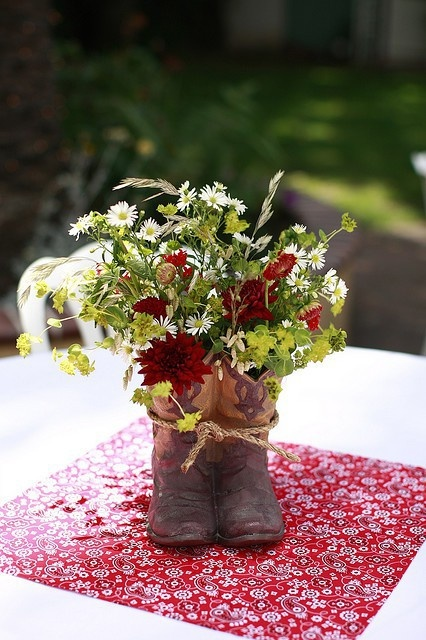 Turn a pair of old cowboy boots into planters. I like how they are tied together with rope.