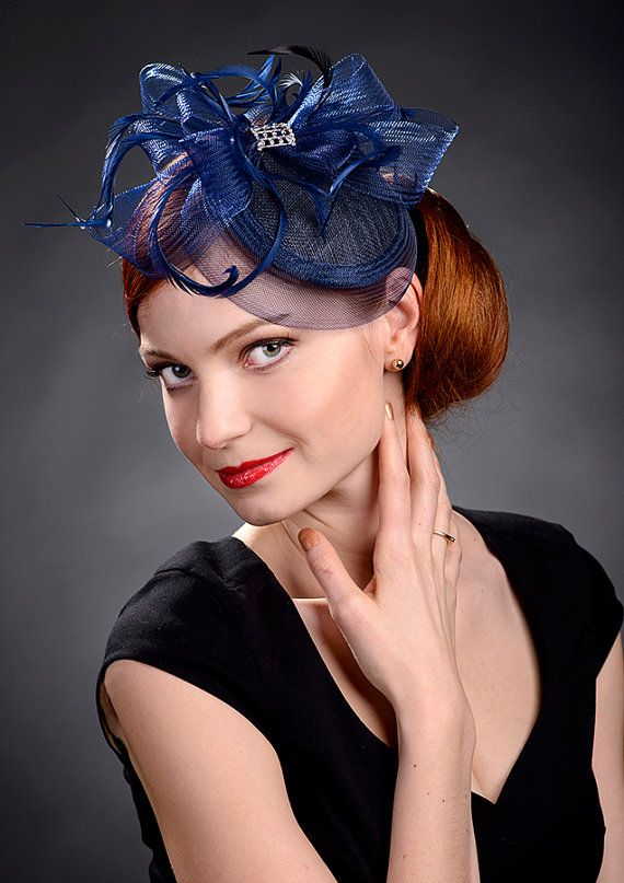 Navy blue small fascinator hat for weddings, bridesmaids, Ascot, Derby, garden parties, church etc. Elegant, simple and beautiful small hat on a metal comb trimmed with curled goose feathers and pretty crystal stone brooch. Fits to any headsize and can be placed anywhere on your head.  Colour of the hat allows matching with many different outfits and styles of garments.  This hat on the picture is ready for immediate delivery. Comes in a nice small gift box where you can store it when not…
