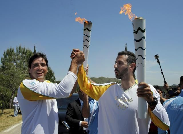 Olympic flame second torch bearer, former volleyball player Giovane Gavio from Brazil (L), passes the torch to third bearer Dimitrios Mougios as they attend the Olympic flame lighting ceremony for the Rio 2016 Olympic Games on the site of ancient Olympia, Greece, April 21, 2016. REUTERS/Yannis Behrakis