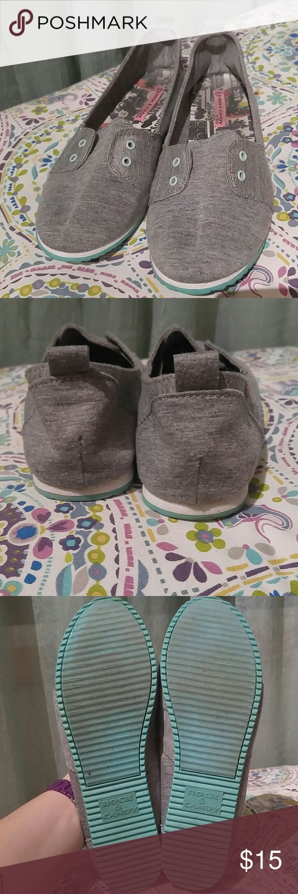 Rock & Candy slip ons gy ZiGi This is a very gently loved pair of gorgeous gray, aqua, and white slip on tennis shoes by Rock & Candy by ZiGi. They don't require laces they have elastic to hold the tongue in place. Rock & Candy by ZiGi Shoes Sneakers