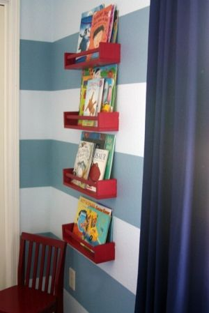 ikea $4 spice racks used as bookshelves...what a great idea! I love the blue stripes and red shelves!