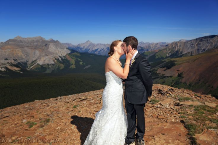 Bride & groom sharing a kiss on the mountain top in Canmore, Alberta. Summer heli-wedding. Canmore Alberta wedding.