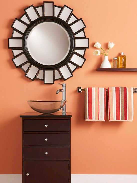 Freshen your bathroom with low-cost updates. Wake Up the Walls with Color: Give a ho-hum bathroom a color transfusion. The dark wooden fixtures in this bathroom are perfect companions for bright hues, such as the bright peach shown here. A statement mirror is a showstopping feature in this bathroom. The mirror, a bold wall color, and vibrant striped towels make for an easy and affordable new look.