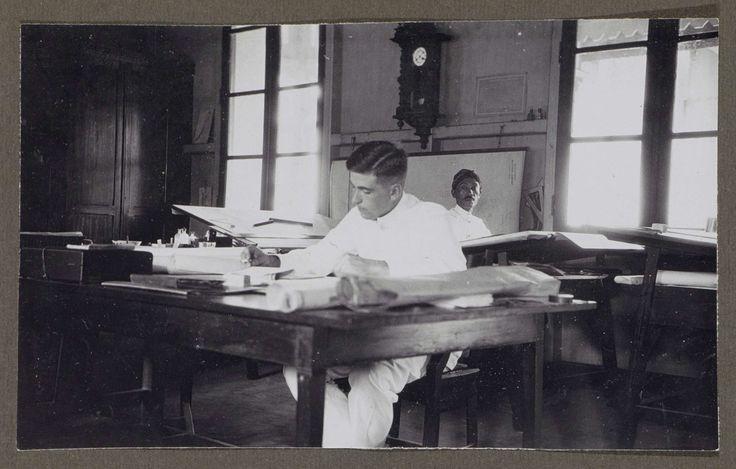 Anonymous | Mannen werkend in een kantoorruimte, Anonymous, 1920 - 1930 | Een man zit met een sigaret in de hand achter een tafel. Hij draagt witte kledij. Voor hem liggen grote vellen papier, een map en een doos. Achter hem zit een Indische man aan een schrijftafel, onder een wandklok. Links in de hoek staat een schrijftafel, mogelijk een ontwerptafel. Onderdeel van Familiealbum Nederlands-Indië.