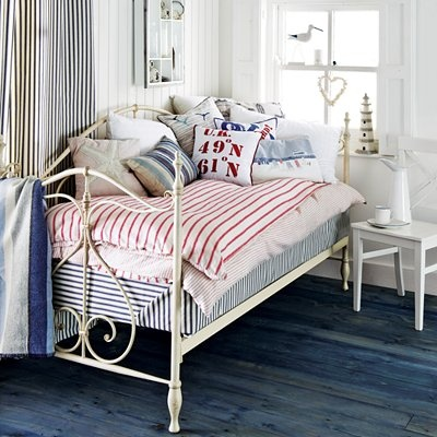 Beautifully accessorised day bed for a guest room with a seaside theme.