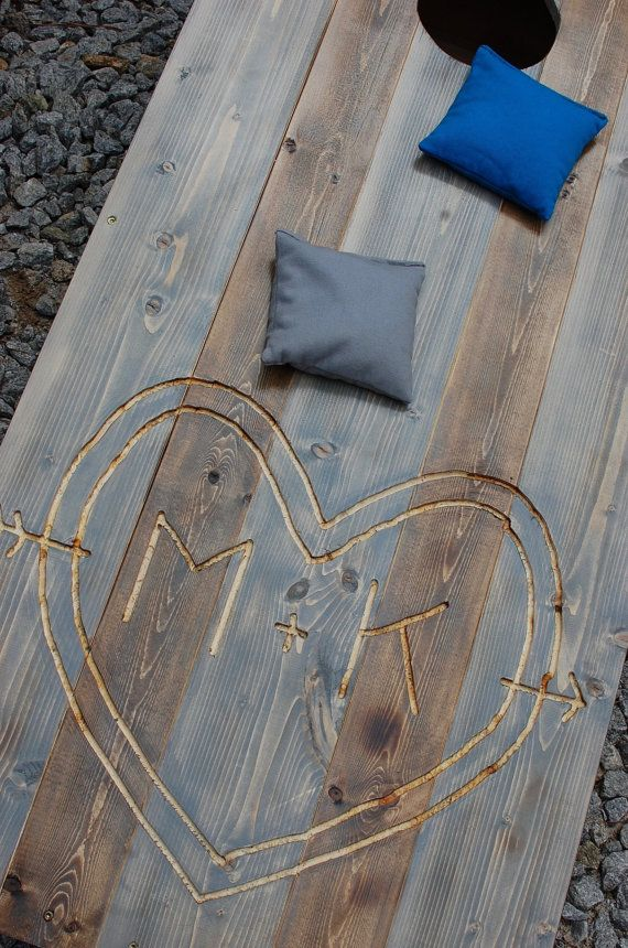 Custom Cornhole Boards & Bean Bag Toss Game  Grab a friend, get outside, grab a cocktail and lets play! These custom cornhole boards were made for a wedding to use as decor and of course play at the cocktail hour. Also a great gift for friends, family or just for your backyard cookouts.  Boards are made from top grade wood and design is routed out by hand. Made with a mix of 1 x4 and 1 x 6 boards while also torching the wood. Planks are stained in classic gray and expresso - which you can…