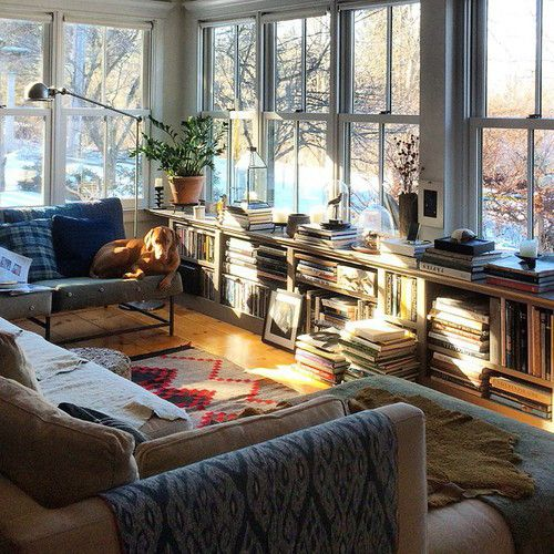 living room | shelving under wall of windows; two walls of windows around seating area, so lovely