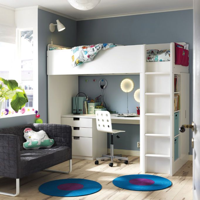 A room with a white loft bed combination that includes a desk, chest of drawers and a wardrobe. Shown together with a small grey sofa and braided round rugs in turquoise/lilac.