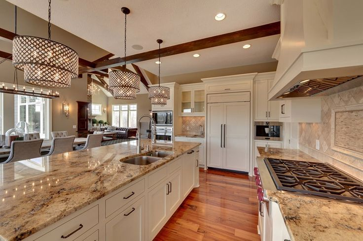 Kitchen with sienna beige granite counters, white cabinetry and contemporary design shade lamps.