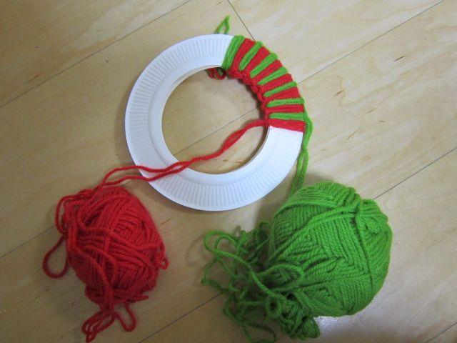 紙皿に毛糸をタッチング結びで巻きつけたリースの作り方です。