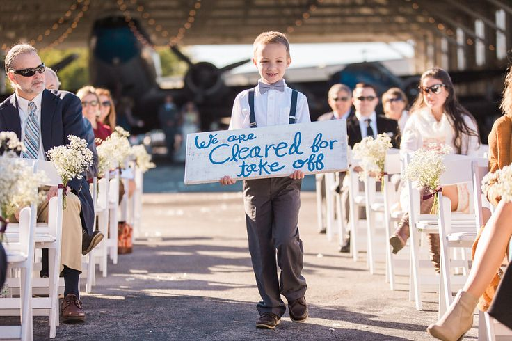 "Ring Bearer walking down the ""runway"". Airplane Hangar wedding."