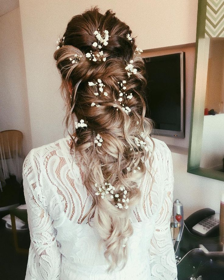 Messy Twists with Floral Accents ---- This whimsical bridal hairstyle is perfect for free-spirited brides. Smooth, twisted knots make this a polished look, while loose curls and baby's breath show the bride's fun and spirited side. Ombre highlights add depth to this hairstyle, as do touches of caramel and platinum blonde.