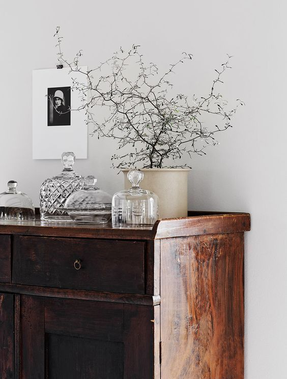 Antique wood dresser styled with black and white photograph, vintage jars, and a potted tree - Home Decor Details