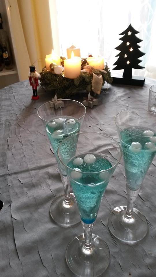 Weihnachtscocktail -  Etwas Blue Curacao mit Champagner auffüllen. Mit kleinen Eiskugeln (1 cm)  als Schneebälle dekorieren