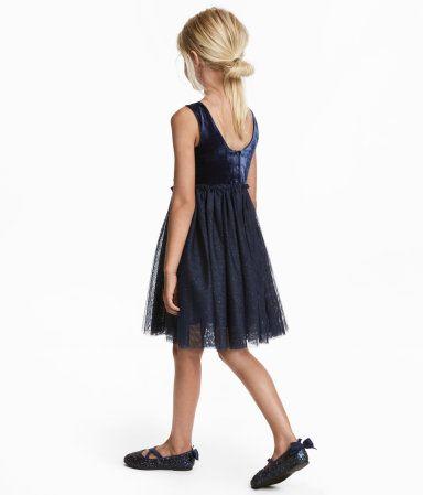 Dunkelblau. Kleid mit mehrlagigem, glitzerndem Tüllrock. Das Kleid hat hinten einen Rundausschnitt mit Knöpfen und in der Taille eine geraffte Naht mit