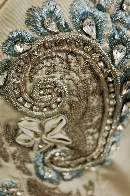 Detail from the bodice ~ A Pierre Balmain couture ball gown, circa 1953-6, the gown of silver-grey silk faille with strapless bodice and full skirt with lavish Lesage silver and blue embroidery with raisedwork C scrolls studded with pastes, satin rosettes, metallic blue embroidery, simple bow to the front