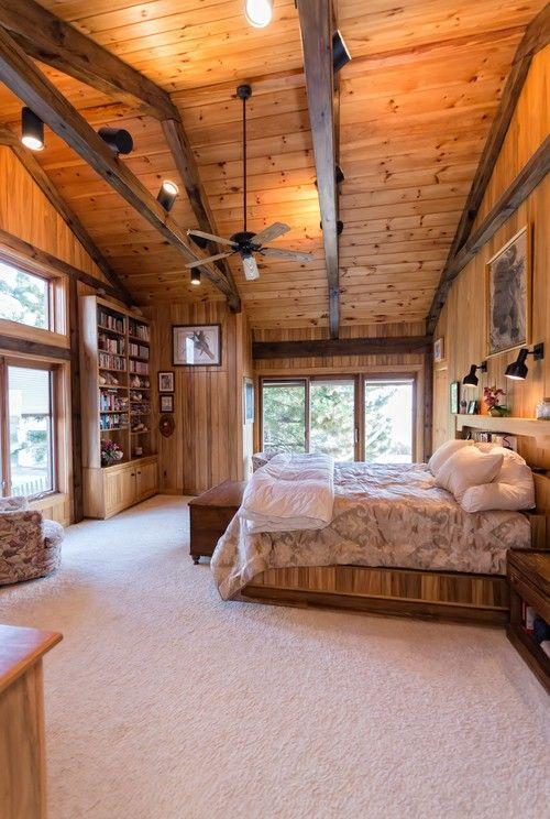 Dieses rustikale Schlafzimmer wirkt leicht und luftig durch die großzügige Verwendung von großen Fenstern, Glastüren und hellen Tönen aus Holz. Foto: SMB Immobilien Fotografie