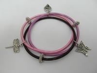 Spiraal armband met diverse metalen bedeltjes.