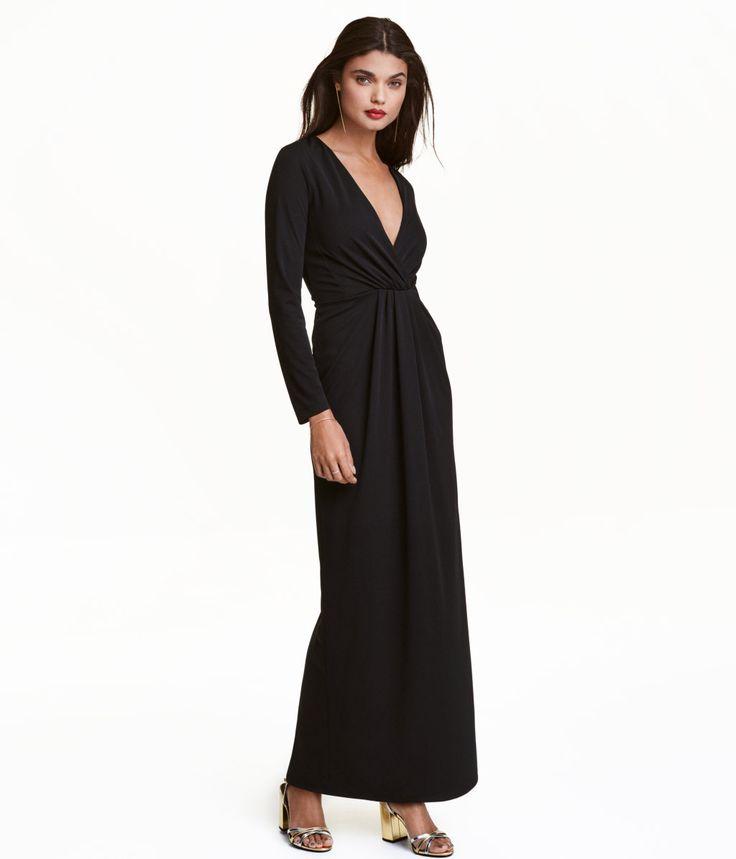 Sort. Lang kjole i kraftig jersey med drapering foran. Kjolen har dyb V-udskæring og slå om-detalje foroven med faste indlæg ved brystet. Lange ærmer og