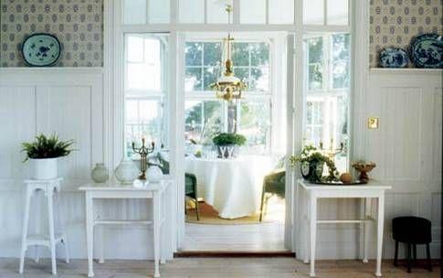 Symmetri Matsalen har fantastisk utsikt. En jugendlampa i mässing hänger över bordet och de små tidstypiska vitmålade borden på varje sida om dörren är fynd från olika loppisar.