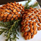 Holiday Pine Cone Cheeseball Recipe. I've made this the past two years, and it was a major hit on both occasions! Second time I used pecans, and they looked awesome too. I think we have a new tradition here.