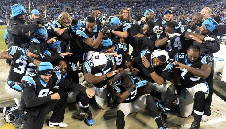Members of the Carolina Panthers dab as they pose for a photo while celebrating their impending victory over the Tampa Bay Buccaneers late in the fourth quarter at Bank of America Stadium on Sunday, January 3, 2016. The Panthers won 38-10, and secured home field through the playoffs.