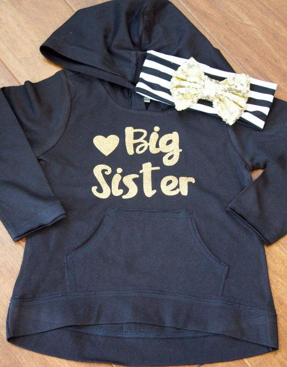 Adorable Big Sister Hoodie. Black Hoodie shown with gold lettering.  Cute High Low Hooded Shirt made of a cotton/polyester blend. This is a nice